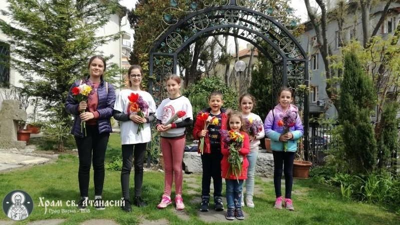 """Деца от енрията при храма """"Св. Атанасий"""" посрещат Цветница в двора на храма с букети цветя"""